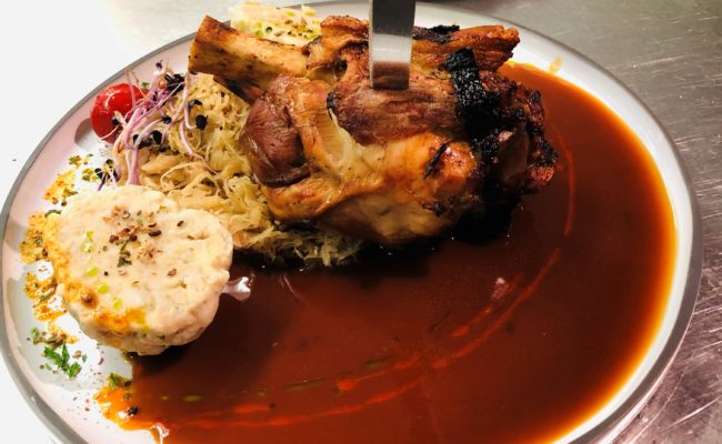 Ofenfrische Schweinshaxe an Dunkelbiersoße mit Sauerkraut und Semmelknödel